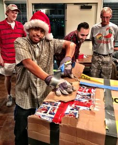 Eddie working hard to open a Christmas gift at the party.